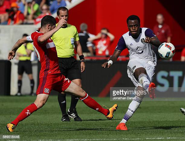 Cyle Larin of Orlando City FC passes around Razvan Cocis of Chicago Fire during an MLS match at Toyota Park on August 14 2016 in Bridgeview Illinois...