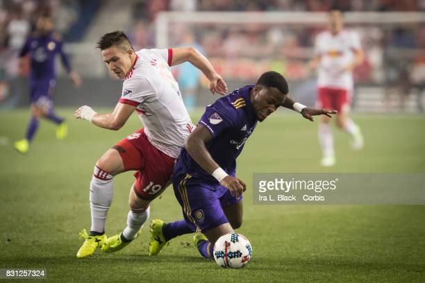 Cyle Larin of Orlando City SC and Alex Muyl of New York Red Bulls fall down trying to get control of the ball during the MLS match between New York...