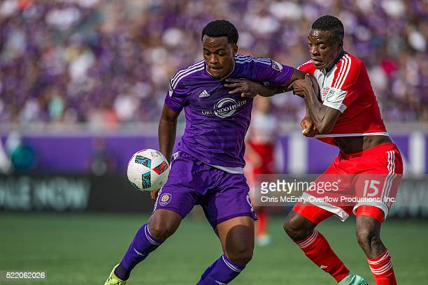 Cyle Larin of the Orlando City Lions defends the ball from JeVaughn Watson of the New England Revolution at the Citrus Bowl in Orlando Florida on...