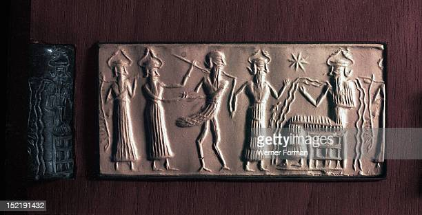 Cylinder seal of the water god Ea with streams flowing from his body It illustrates the myth in which the bird man Zu is led before his judge Ea for...