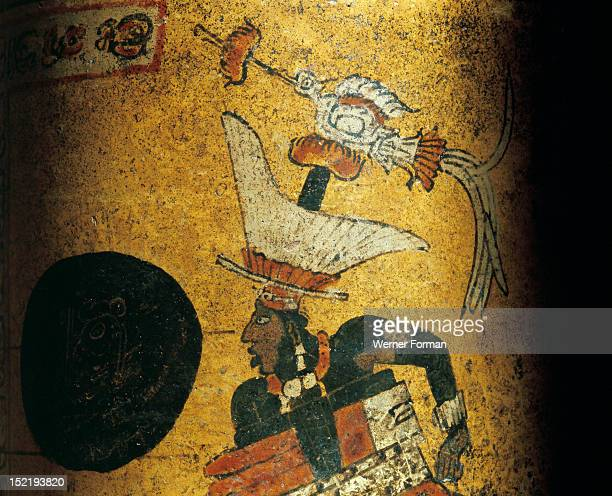 Cylindrical vessel decorated a Mayan ball player wearing black body paint and heavy padding for the competition The great yoke protecting the ball...