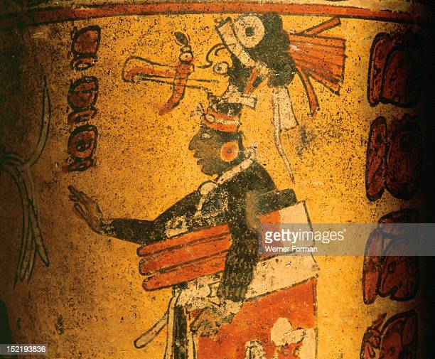 Cylindrical vessel decorated with date glyphs and a Mayan ball player wearing black body paint and heavy padding for the competition The great yoke...