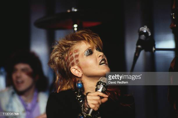 Cyndi Lauper US singersongwriter singing into a microphone silver makeup on her lips and eyelids at the Montreux Rock Festival in Montreux...