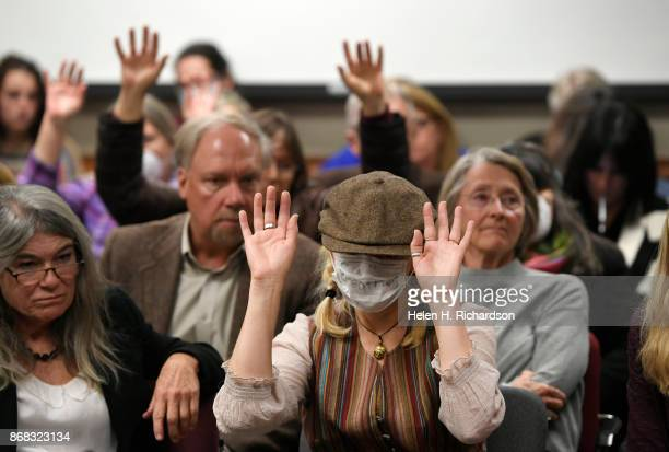 DENVER CO OCTOBER 30 Cyndy Nusbaum middle wearing a mask to show her opposition to COGCC board members waves her hands in the air with others to...
