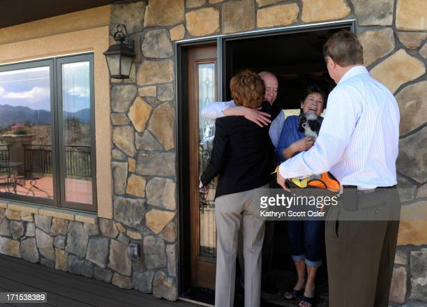 Cynthia and Bill Flanagan and their toy poodle 'Ruby' greet the mayor and his wife at the front door of their newly built home The two were able to...