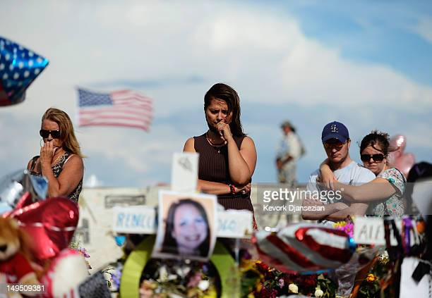 Cynthia Davis gets emotional as she visits the roadside memorial set up for victims of the Colorado theater shooting massacre across the street from...