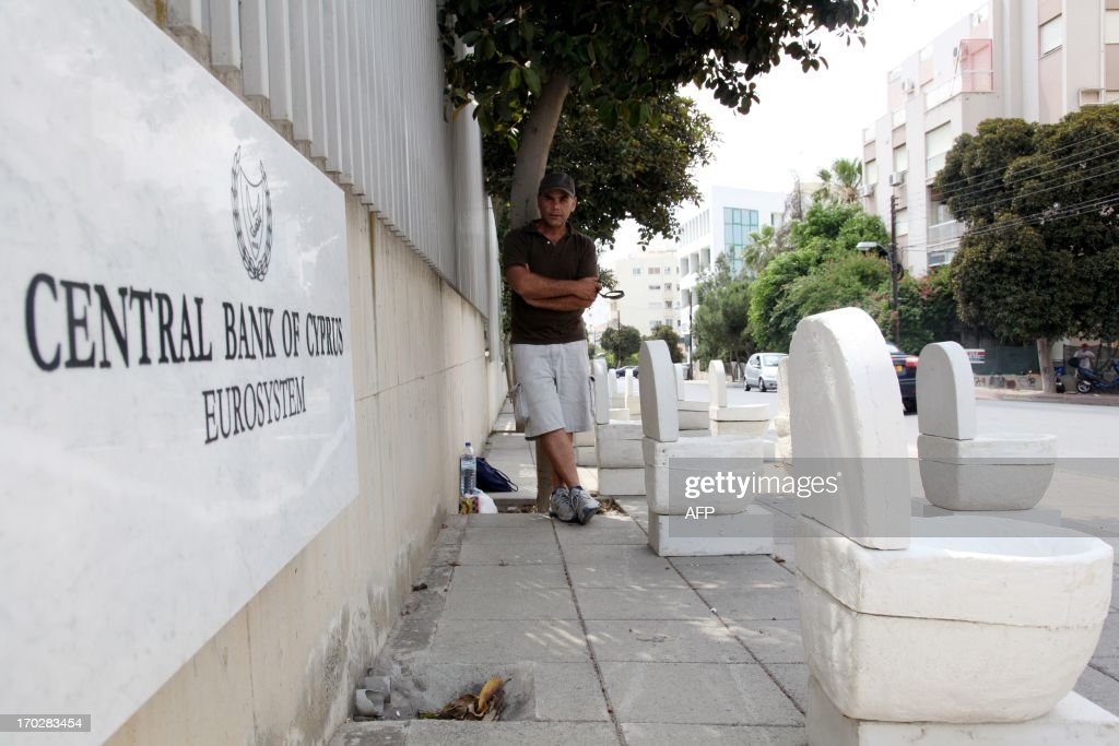 Cypriot artist Andreas Efstathiou poses next to his artwork of plaster toilets displayed outside the Cyprus Central Bank in Nicosia on June 10, 2013 in an unusual protest to signal the island's bailout economy is going down the pan. Efstathiou called it a 'symbolic protest' to highlight the pain Cypriots have suffered since Cyprus secured 10 billion euros ($13 billion) in European Union rescue aid in return for an unprecedented bail-in from bank depositors.