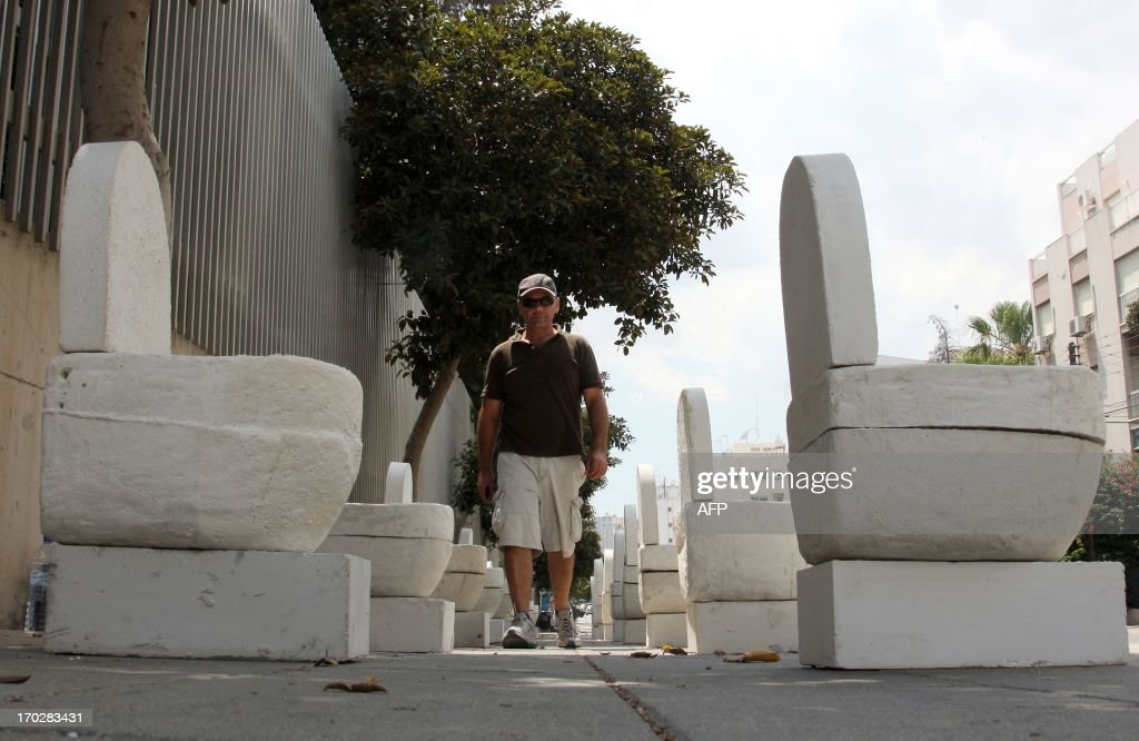 Cypriot artist Andreas Efstathiou walks past his artwork of plaster toilets displayed outside the Cyprus Central Bank in Nicosia on June 10, 2013 in an unusual protest to signal the island's bailout economy is going down the pan. Efstathiou called it a 'symbolic protest' to highlight the pain Cypriots have suffered since Cyprus secured 10 billion euros ($13 billion) in European Union rescue aid in return for an unprecedented bail-in from bank depositors.