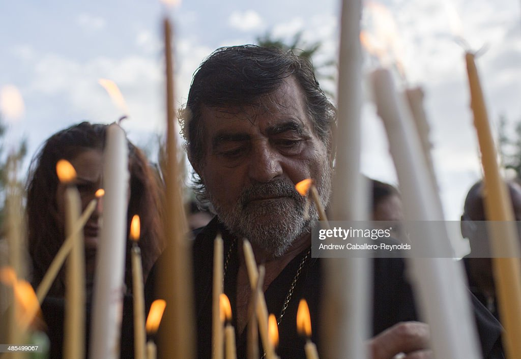 A Cypriot Christian Orthodox lights a candel before a Good Friday procession, at the Ayios Georgios Exorinos Church in the Cypriot Turkish controlled North on April 17, 2014 in Famagusta, Cyprus. More than 4000 people attended the service, the first since 1957 at the church in the medieval town. Organizers tried to make the Good Friday service an example of how religion can bring both sides together.