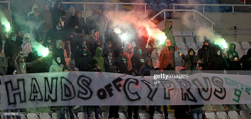 Cypriot football fans hold a banner reading 'Hands off Cyprus' while lighting flares during the 2014 World Cup European zone group E qualifying football match between Cyprus and Switzerland at GSP Stadium in Nicosia on March 23, 2013. The group of fans came into the stadium briefly for a protest as parliament debated a bailout to save the island from bankruptcy.