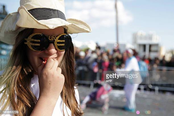 A Cypriot girl wearing glasses framed by the Euro logo takes part in an annual carnival in the southern Cypriot port of Limassol Cyprus postponed an...