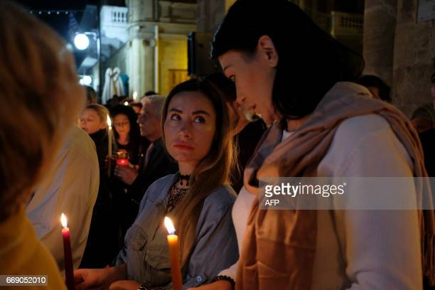 Cypriot Greek Orthodox worshippers stand outside Faneromeni church in the old city of Nicosia carrying candles during the Easter Saturday vigil after...
