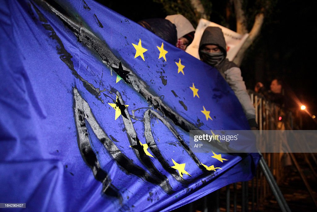 A Cypriot man carries the EU flag with the word 'No' written on it during a protest outside the parliament building in the capital Nicosia on March 22, 2013. Cyprus' two biggest lenders urged lawmakers to adopt a tax on bank deposits, a controversial deal with the EU that the MPs rejected this week, as their employees protested outside parliament.