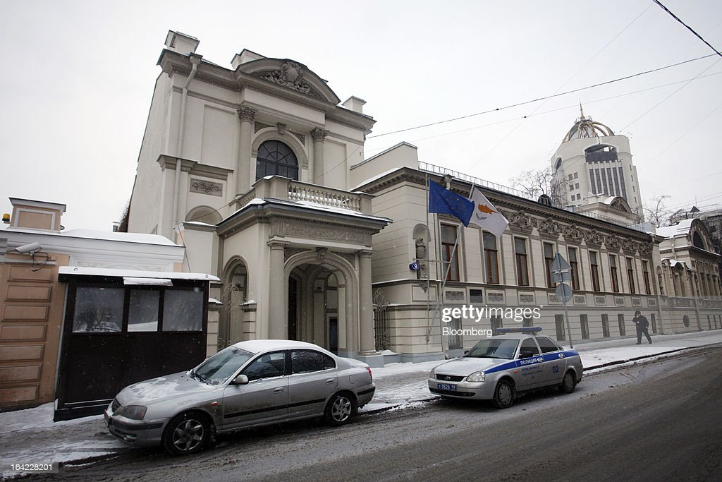 A Cypriot national flag flies alongside a European Union (EU) flag outside the Cypriot embassy building in Moscow, Russia, on Thursday, March 21, 2013. Cyprus is offering Russia 'opportunities' including banking and natural gas assets after lawmakers rejected a levy on bank deposits imposed by euro-area finance ministers, Finance Minister Michael Sarris said today in Moscow. Photographer: Alexander Zemlianichenko Jr/Bloomberg via Getty Images