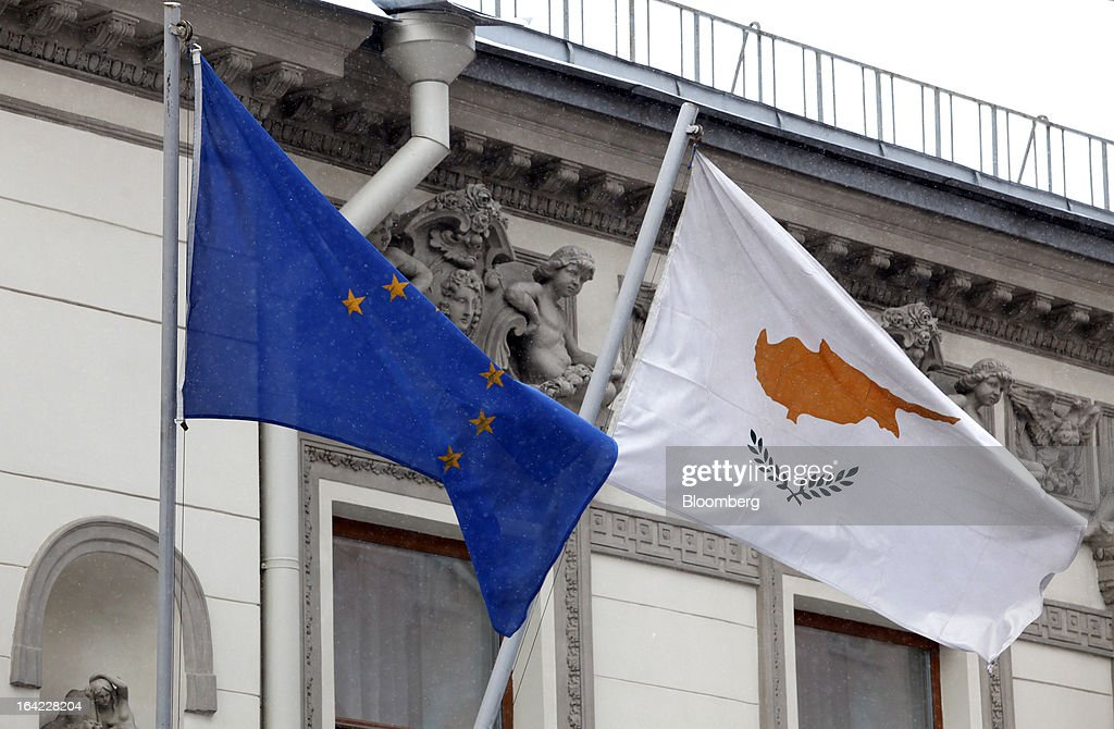 A Cypriot national flag, right, flies alongside a European Union (EU) flag outside the Cypriot embassy building in Moscow, Russia, on Thursday, March 21, 2013. Cyprus is offering Russia 'opportunities' including banking and natural gas assets after lawmakers rejected a levy on bank deposits imposed by euro-area finance ministers, Finance Minister Michael Sarris said today in Moscow. Photographer: Alexander Zemlianichenko Jr/Bloomberg via Getty Images