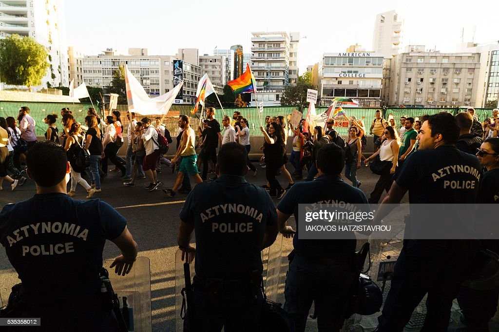 Cypriot police stand guard as people march during the third edition of the Gay Pride parade on May 29, 2016 in Cyprus' capital Nicosia. / AFP / Iakovos Hatzistavrou