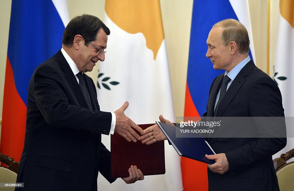 Cypriot President <a gi-track='captionPersonalityLinkClicked' href=/galleries/search?phrase=Nicos+Anastasiades&family=editorial&specificpeople=10113933 ng-click='$event.stopPropagation()'>Nicos Anastasiades</a> (L) and Russian President <a gi-track='captionPersonalityLinkClicked' href=/galleries/search?phrase=Vladimir+Putin&family=editorial&specificpeople=154896 ng-click='$event.stopPropagation()'>Vladimir Putin</a> exchange documents during a signing ceremony at the Novo-Ogaryovo residence outside Moscow on February 25, 2015. AFP PHOTO / YURI KADOBNOV