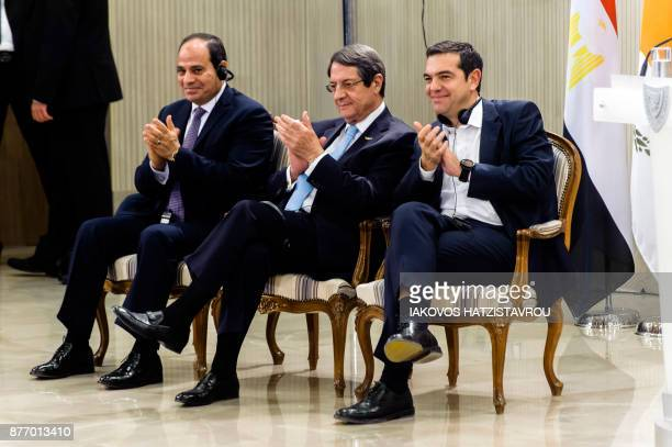 Cypriot President Nicos Anastasiades Greek prime minister Alexis Tsipras and Egyptian President Abdel Fattah alSisi clap their hands during a press...