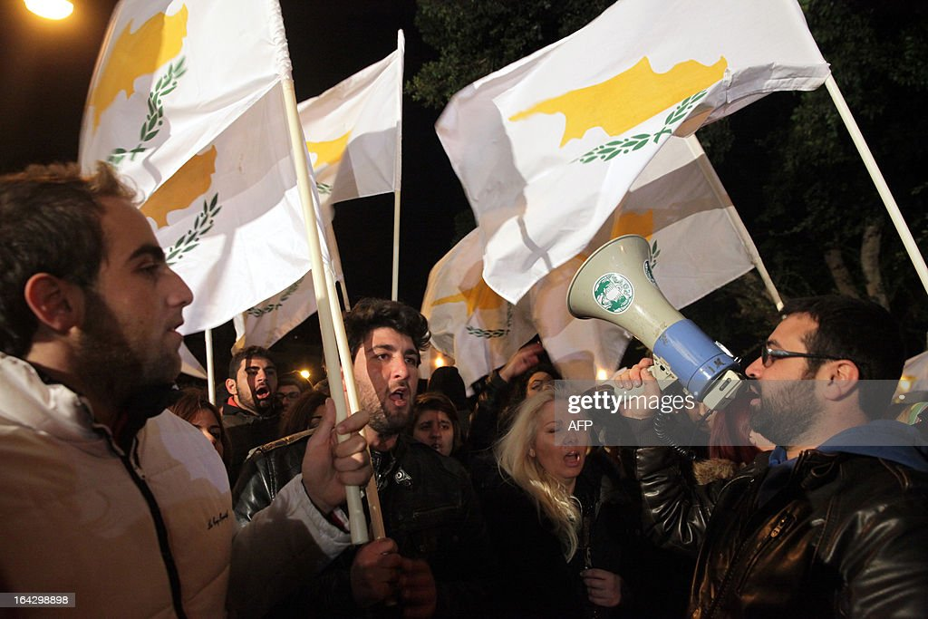 Cypriot protesters shout slogans during a protest outside the parliament building in the capital Nicosia on March 22, 2013. Cyprus plans a tax of up to 15 percent on bank deposits as part of a deal to secure bailout funds, state television said, after Russia spurned its plea for an economic lifeline to stave off bankruptcy.