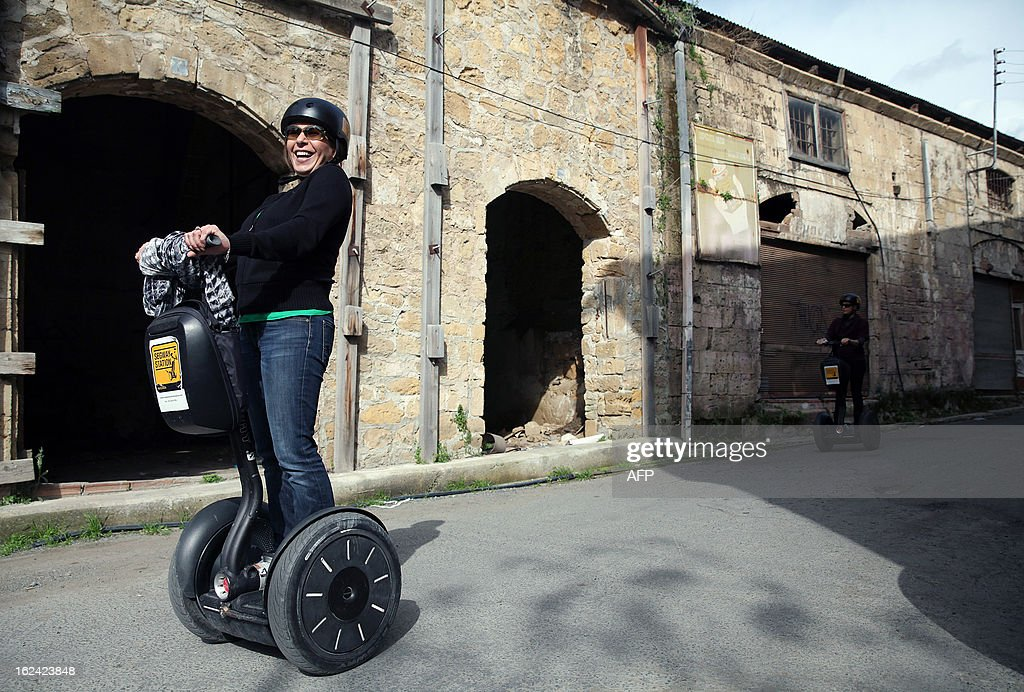 Cypriot tourists ride Segways in the old part of the capital, Nicosia, one day before the second run-off of the Cypriot presidential elections on February 23, 2013. A second-round on February 24, being closely watched in European capitals pits right-wing opposition leader Nicos Anastasiades against Stavros Malas, who is backed by the communist party in power during the economic downturn, Akel. AFP PHOTO / YIANNIS KOURTOGLOU