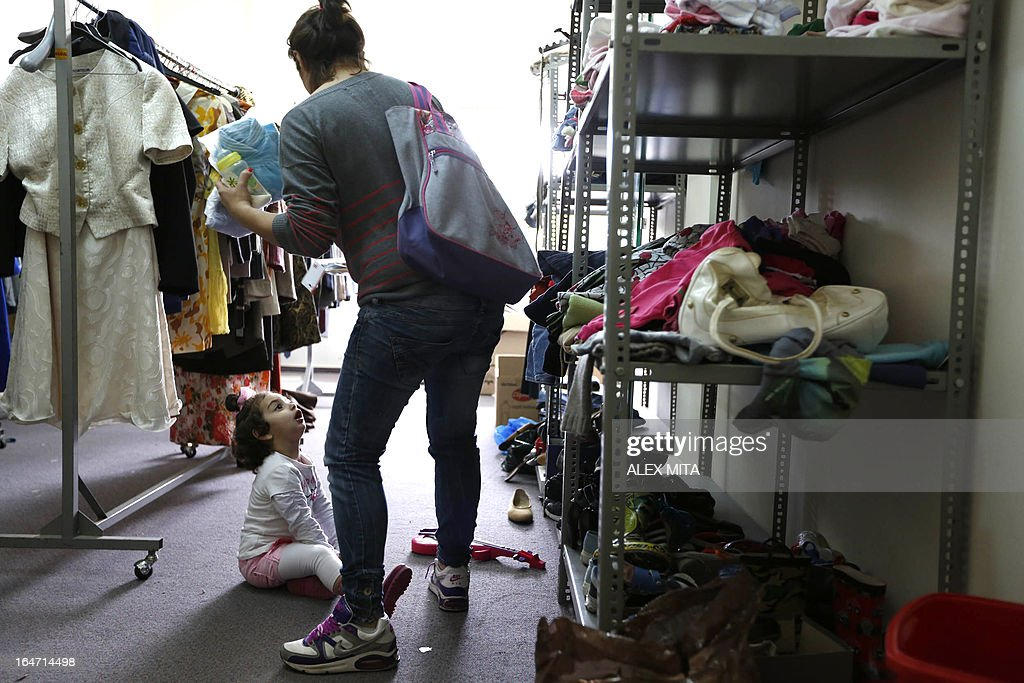 A Cypriot woman and her daughter choose clothes at the Cyprus Red Cross in Nicosia, on March 27, 2013. Cyprus secured a 10-billion-euro ($13-billion) bailout from the European Union and International Monetary Fund earleir this week that saved the eurozone member from bankruptcy. AFP PHOTO/ALEX MITA