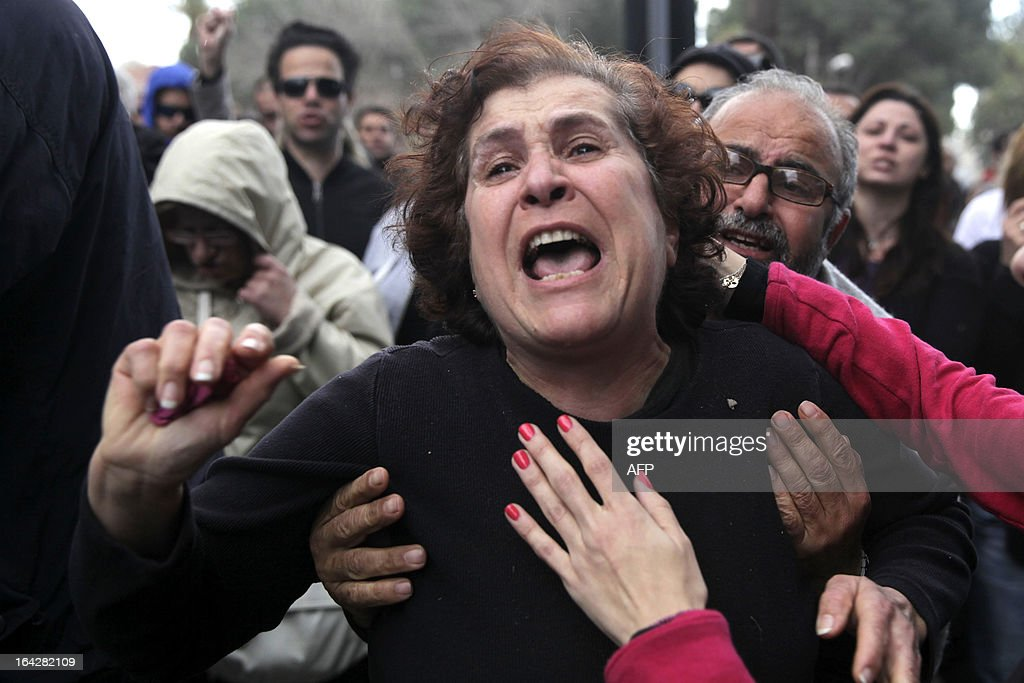 A Cypriot woman gets emotional during a protest outside the parliament building in the capital Nicosia on March 22, 2013. Cyprus' two biggest lenders urged lawmakers to adopt a tax on bank deposits, a controversial deal with the EU that the MPs rejected this week, as their employees protested outside parliament.