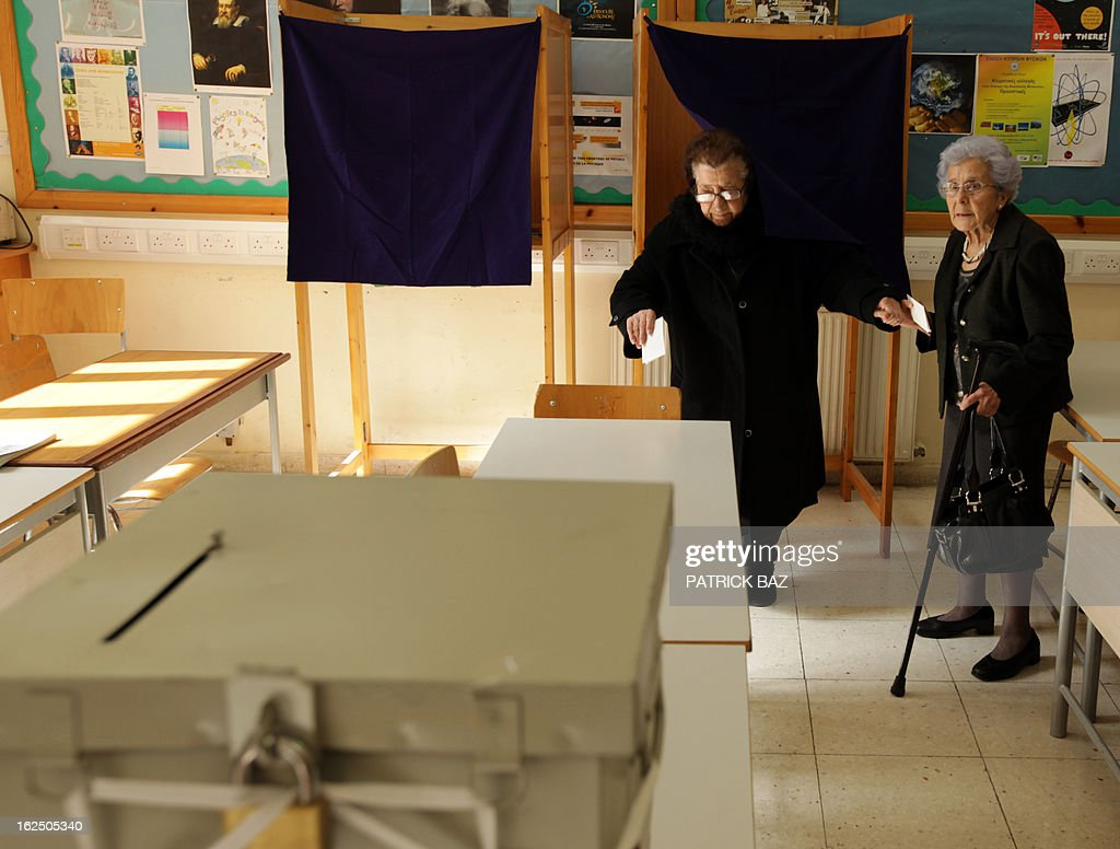 A Cypriot woman helps her friend getting out from a voting booth during the second round of Cyprus' presidential election at a polling station on February 24, 2013 in the walled part of the Cypriot capital, Nicosia. Cypriots trickled in under bright, spring-like sunshine to vote in a left-right presidential runoff for electing a new leader to seal a crucial bailout for the EU state on the brink of bankruptcy. AFP PHOTO PATRICK BAZ
