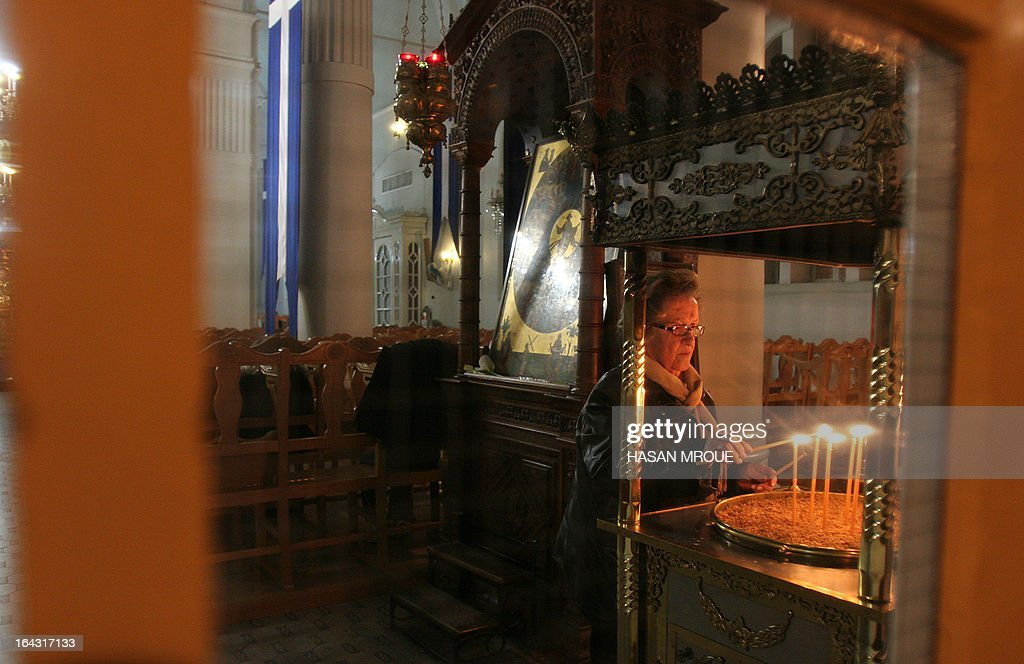 A Cypriot woman lights a candle at Faneromeni Church in the old city of Nicosia on March 22, 2013. Eurozone finance ministers will meet in Brussels on March 24 in a last-ditch bid to find a solution for bankruptcy-threatened Cyprus and fix a broken bailout accord, three separate sources told AFP.