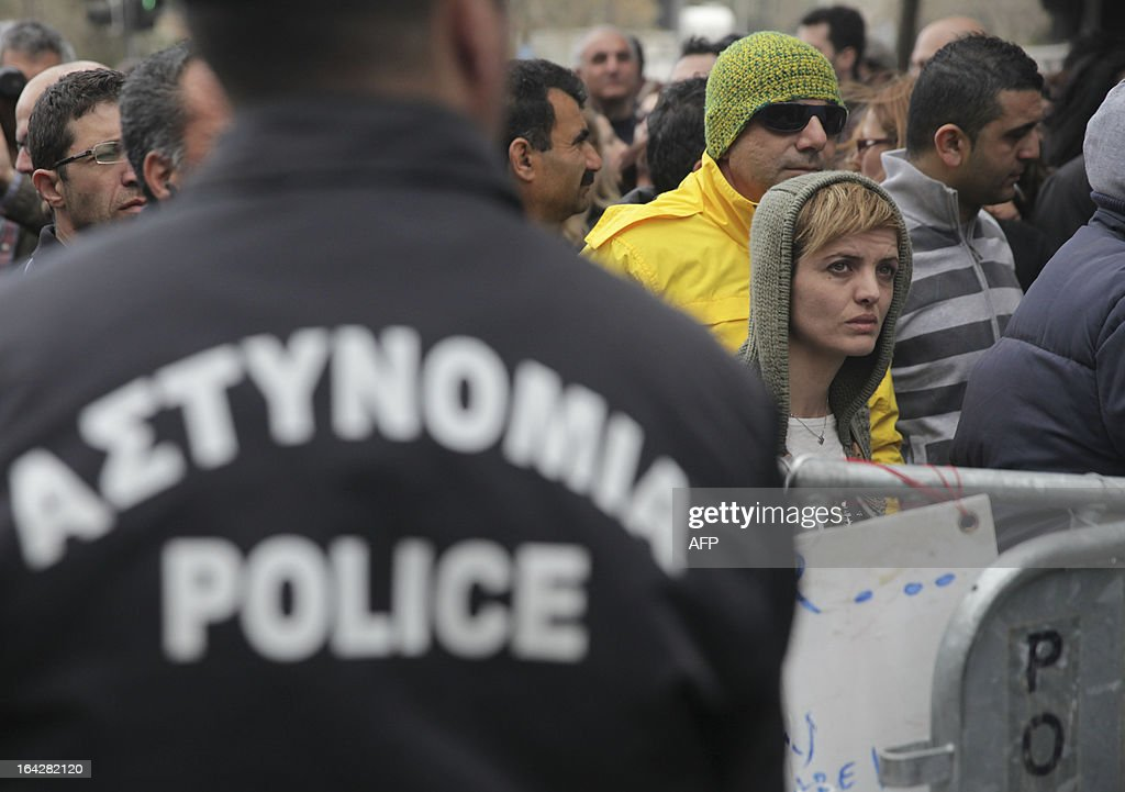Cypriots protest outside the parliament building in the capital Nicosia on March 22, 2013, as the east Mediterranean island' two biggest lenders urged lawmakers to adopt a tax on bank deposits, a controversial deal with the EU that the MPs rejected this week.