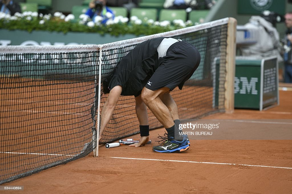 Cyprus' Marcos Baghdatis falls into the net during his men's second round match against France's Jo-Wilfried Tsonga at the Roland Garros 2016 French Tennis Open in Paris on May 26, 2016. / AFP / MARTIN