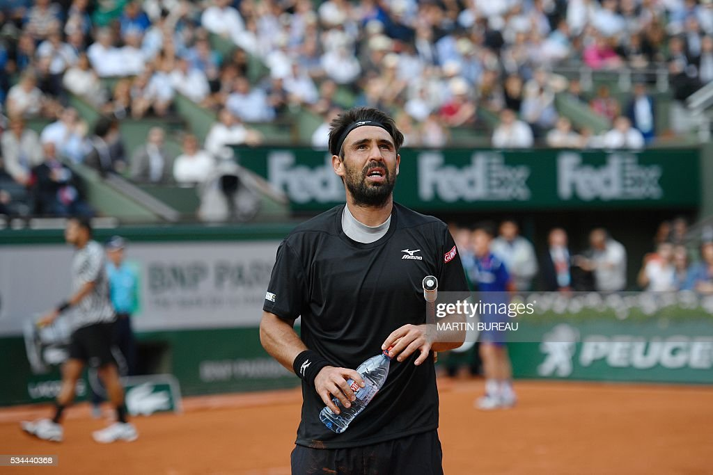 Cyprus' Marcos Baghdatis reacts after losing his men's second round match against France's Jo-Wilfried Tsonga at the Roland Garros 2016 French Tennis Open in Paris on May 26, 2016. / AFP / Martin BUREAU