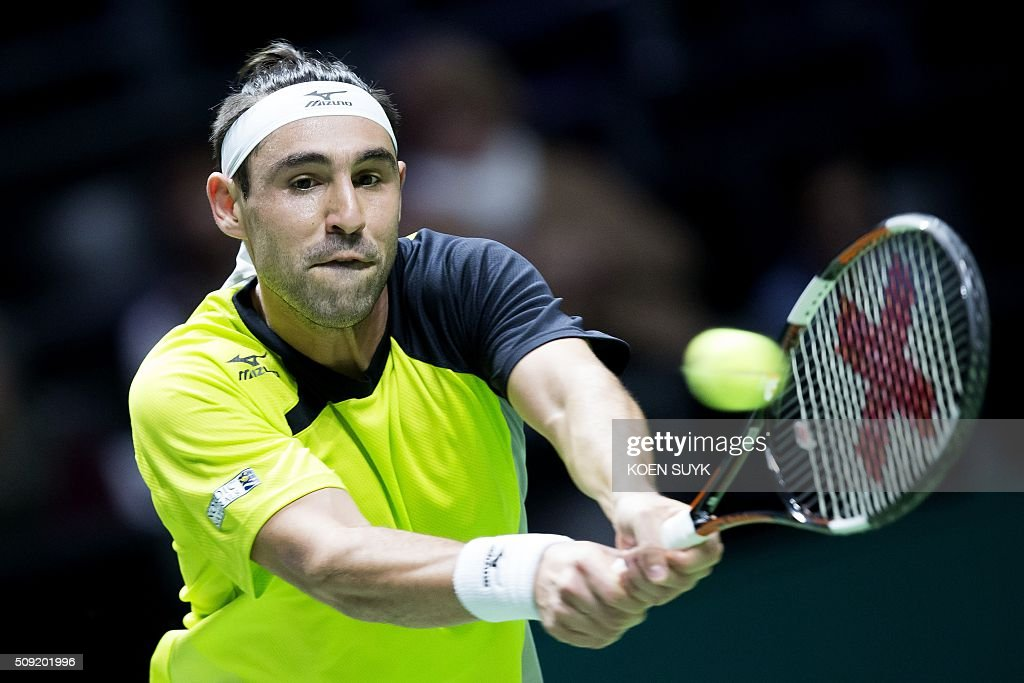 Cyprus' Marcos Baghdatis returns the ball to Belgium's David Goffin during their first round match during the ABN AMRO World Tennis Tournament in Rotterdam, on February 9, 2016. / AFP / ANP / Koen Suyk / Netherlands OUT
