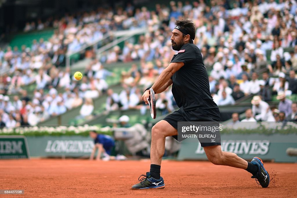 Cyprus' Marcos Baghdatis returns the ball to France's Jo-Wilfried Tsonga during their men's second round match at the Roland Garros 2016 French Tennis Open in Paris on May 26, 2016. / AFP / Martin BUREAU