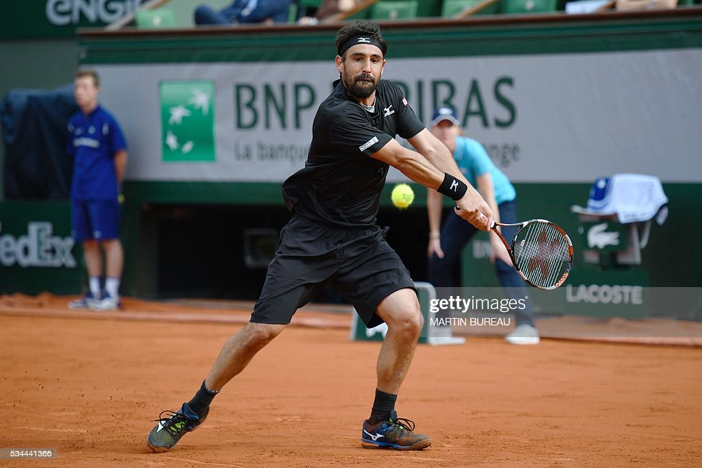 Cyprus' Marcos Baghdatis returns the ball to France's Jo-Wilfried Tsonga during their men's second round match at the Roland Garros 2016 French Tennis Open in Paris on May 26, 2016. / AFP / MARTIN