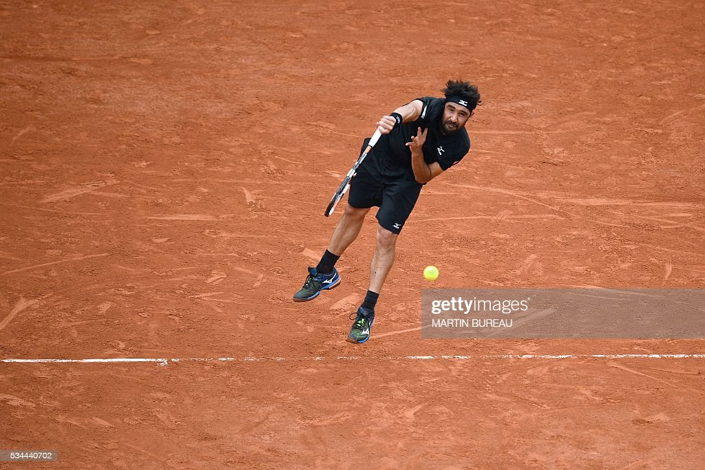 Cyprus' Marcos Baghdatis serves the ball to France's Jo-Wilfried Tsonga during their men's second round match at the Roland Garros 2016 French Tennis Open in Paris on May 26, 2016. / AFP / MARTIN