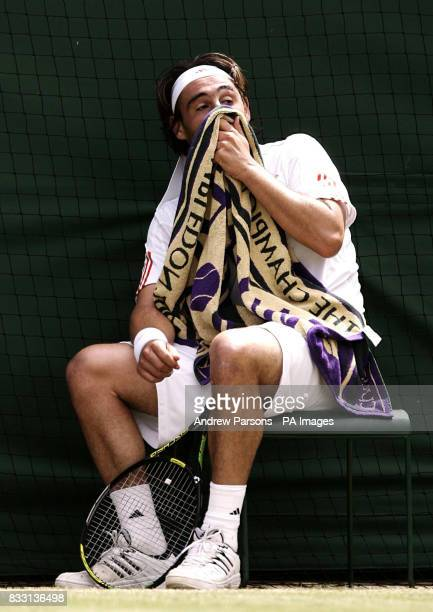 Cyprus' Marcos Baghdatis sits frustrated against Serbia's Novak Djokovic during The All England Lawn Tennis Championship at Wimbledon