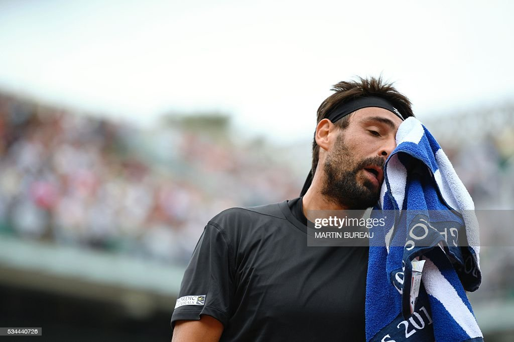Cyprus' Marcos Baghdatis wipes his face with a towel during his men's second round match against France's Jo-Wilfried Tsonga at the Roland Garros 2016 French Tennis Open in Paris on May 26, 2016. / AFP / MARTIN