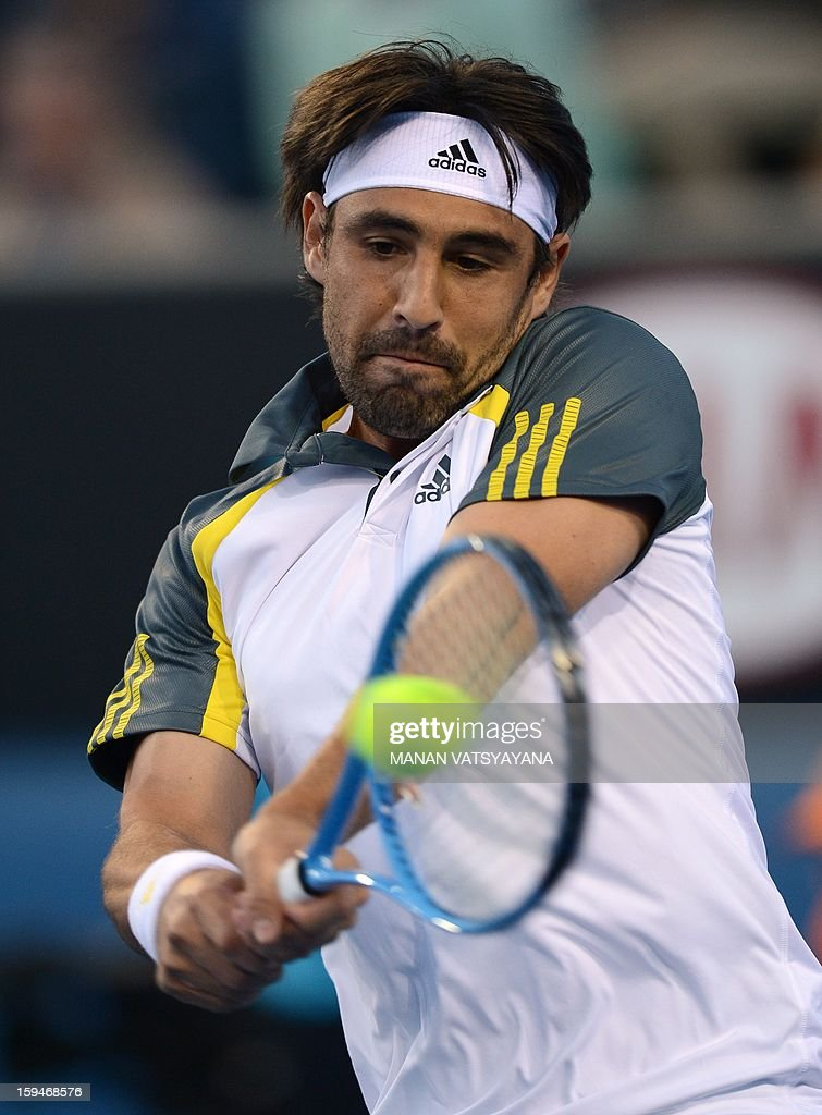 Cyprus's Marcos Baghdatis hits a return against Argentina's Juan Monaco during their men's singles first round match on day one of the Australian Open tennis tournament in Melbourne on January 14, 2013. AFP PHOTO / MANAN VATSYAYANA IMAGE STRICTLY RESTRICTED TO EDITORIAL USE - STRICTLY NO COMMERCIAL USE