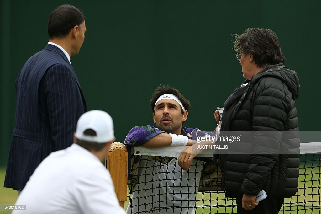 Cyprus's Marcos Baghdatis (C) speaks to the umpire about the state of the weather during a men's singles first round match on the third day of the 2016 Wimbledon Championships at The All England Lawn Tennis Club in Wimbledon, southwest London, on June 29, 2016. / AFP / JUSTIN