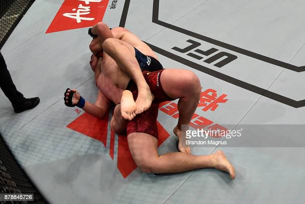 Cyril Asker of France secures a rear choke submission against Hu Yaozong of China in their heavyweight bout during the UFC Fight Night event inside...