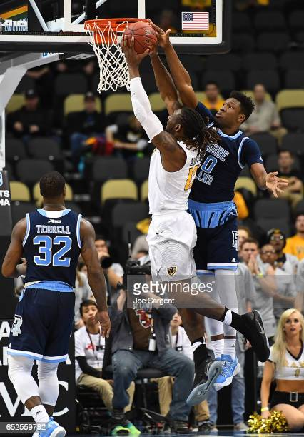 Cyril Langevine of the Rhode Island Rams blocks a shot attempt by Mo AlieCox of the Virginia Commonwealth Rams during the championship game of the...