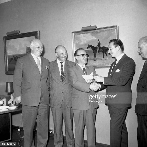Cyril Stein Managing Director of Ladbrokes presents a 4500 cheque to Alderman Alfred Camage Chairman of the Doncaster Racecourse The money will form...