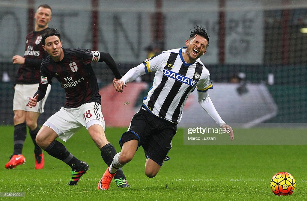 Cyril Thereau (R) of Udinese Calcio competes for the ball with Riccardo Montolivo (L) of AC Milan during the Serie A match between AC Milan and Udinese Calcio at Stadio Giuseppe Meazza on February 7, 2016 in Milan, Italy.