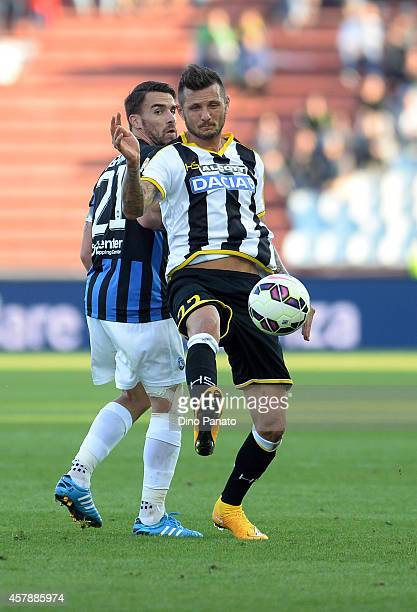 Cyril Thereau of Udinese Calcio competes with Luca Cigarini of Atalanta BC during the Serie A match between Udinese Calcio and Atalanta BC at Stadio...