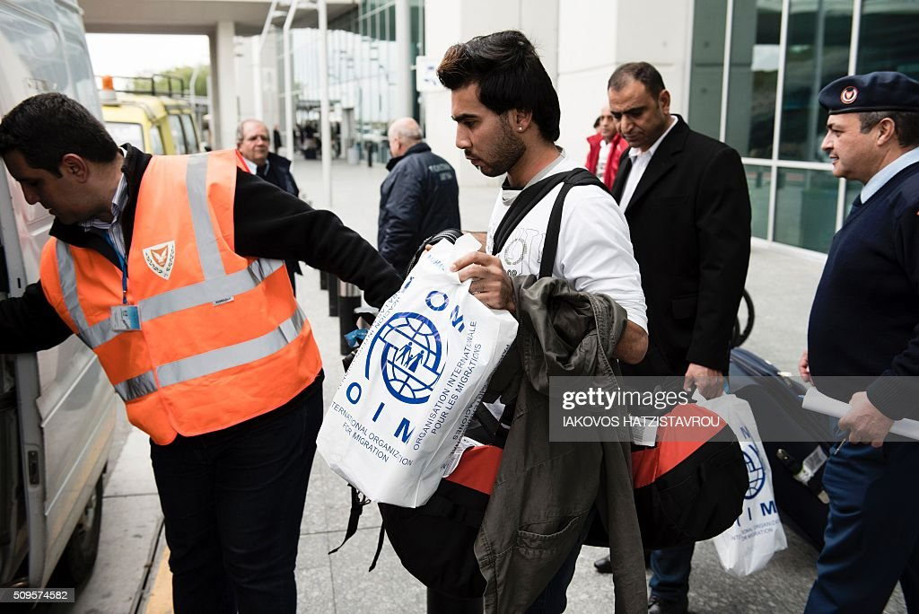 Cyrpiot civilian defence members assist a migrant into a vehicle at the International airport in the Cypriot southeastern port city of Larnaca on February 11, 2016 upon his arrival from Greece alongside five other people as part of the European Union's efforts and its Member States to manage Greece's immigration crisis. Cyprus welcomed the first group of people, in the context of the implementing of a program of relocation of beneficiaries of protection from Greece, consistent with its commitments through the Member States facing disproportionate migratory pressures. / AFP / Iakovos Hatzistavrou