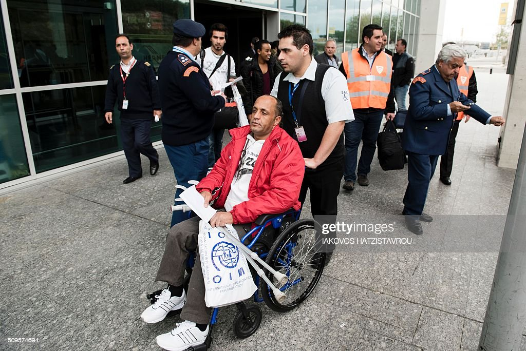Cyrpiot civilian defence members assist a migrant on a wheelchair at the International airport in the Cypriot southeastern port city of Larnaca on February 11, 2016 upon his arrival from Greece alongside five other people as part of the European Union's efforts and its Member States to manage Greece's immigration crisis. Cyprus welcomed the first group of people, in the context of the implementing of a program of relocation of beneficiaries of protection from Greece, consistent with its commitments through the Member States facing disproportionate migratory pressures. / AFP / Iakovos Hatzistavrou
