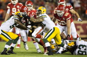 Cyrus Gray of the Kansas City Chiefs is tackled by Chaz Powell of the Green Bay Packers during the last preseason game at Arrowhead Stadium on August...