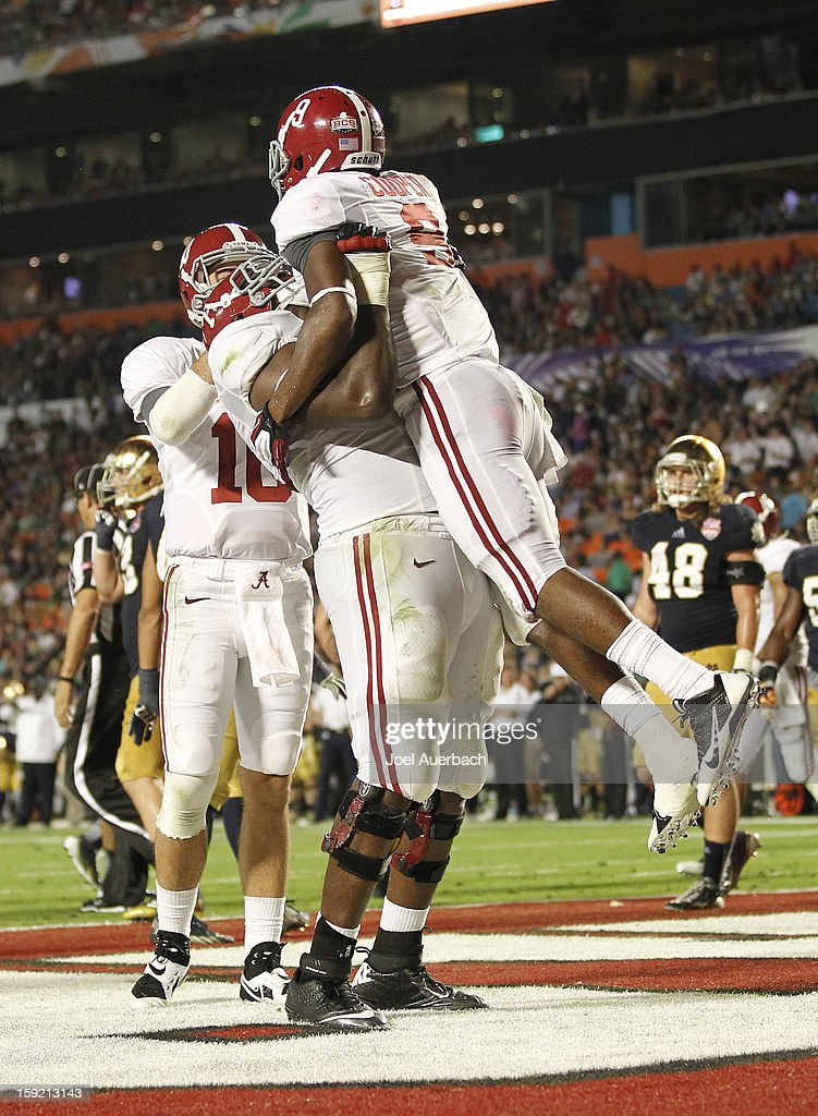 Cyrus Kouandjio #71 of the Alabama Crimson Tide lifts Amari Cooper #9 after Cooper scored a third-quarter touchdown on a 34-yard pass against the Notre Dame Fighting Irish during the 2013 Discover BCS National Championship Game at Sun Life Stadium on January 7, 2013 in Miami Gardens, Florida. Alabama defeated Notre Dame 42-14.