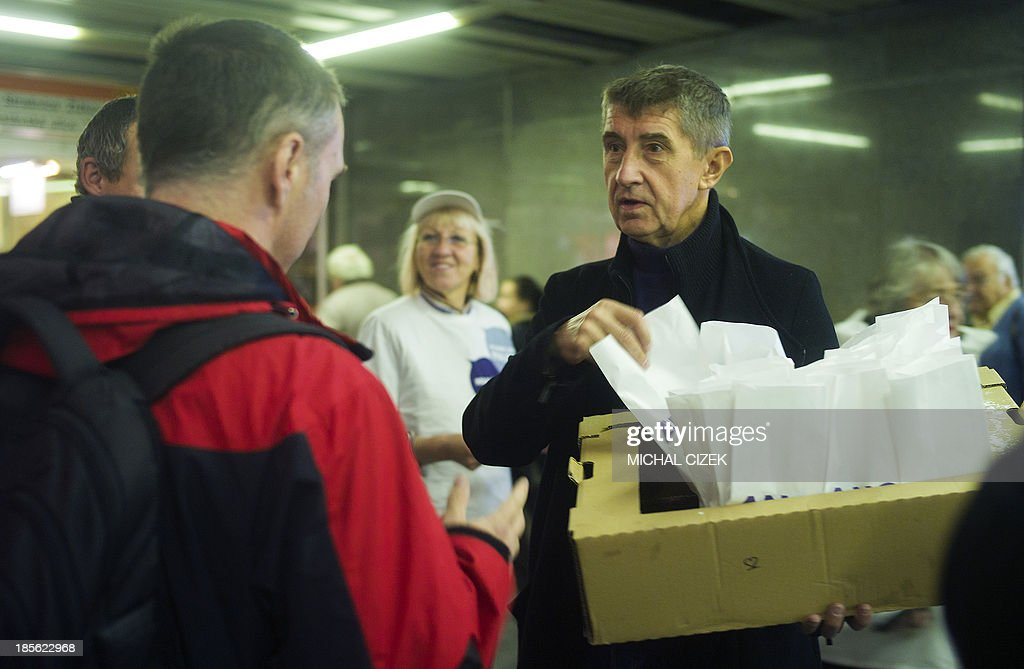 Czech billionaire Andrej Babis (R) hands out donuts during an election campaign of his party ANO ('YES') on October 23, 2013 in Prague, two days ahead of the Czech general elections on October 25 - 26. AFP PHOTO / MICHAL CIZEK