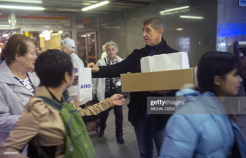Czech billionaire Andrej Babis (C-R) hands out donuts during an election campaign event of his party ANO ('YES') on October 23, 2013 in Prague, two days ahead of the Czech general elections on October 25 - 26.